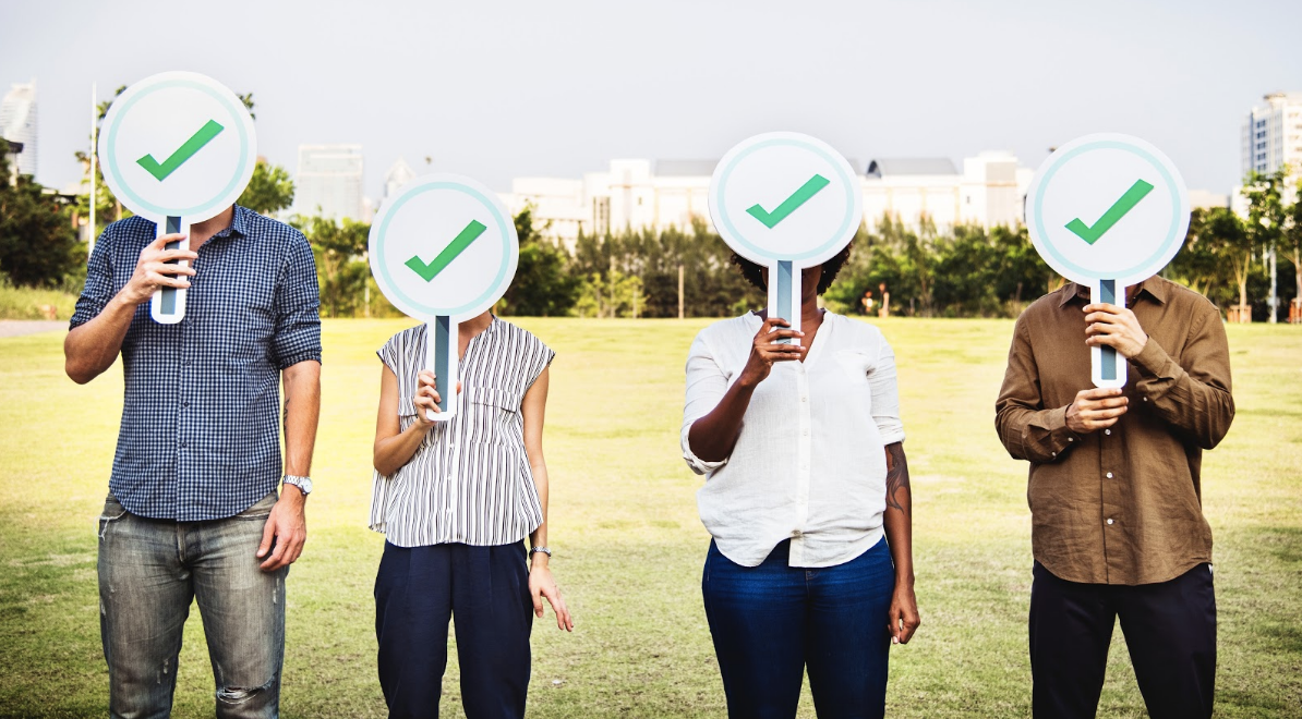 Four people holding green check signs on a field